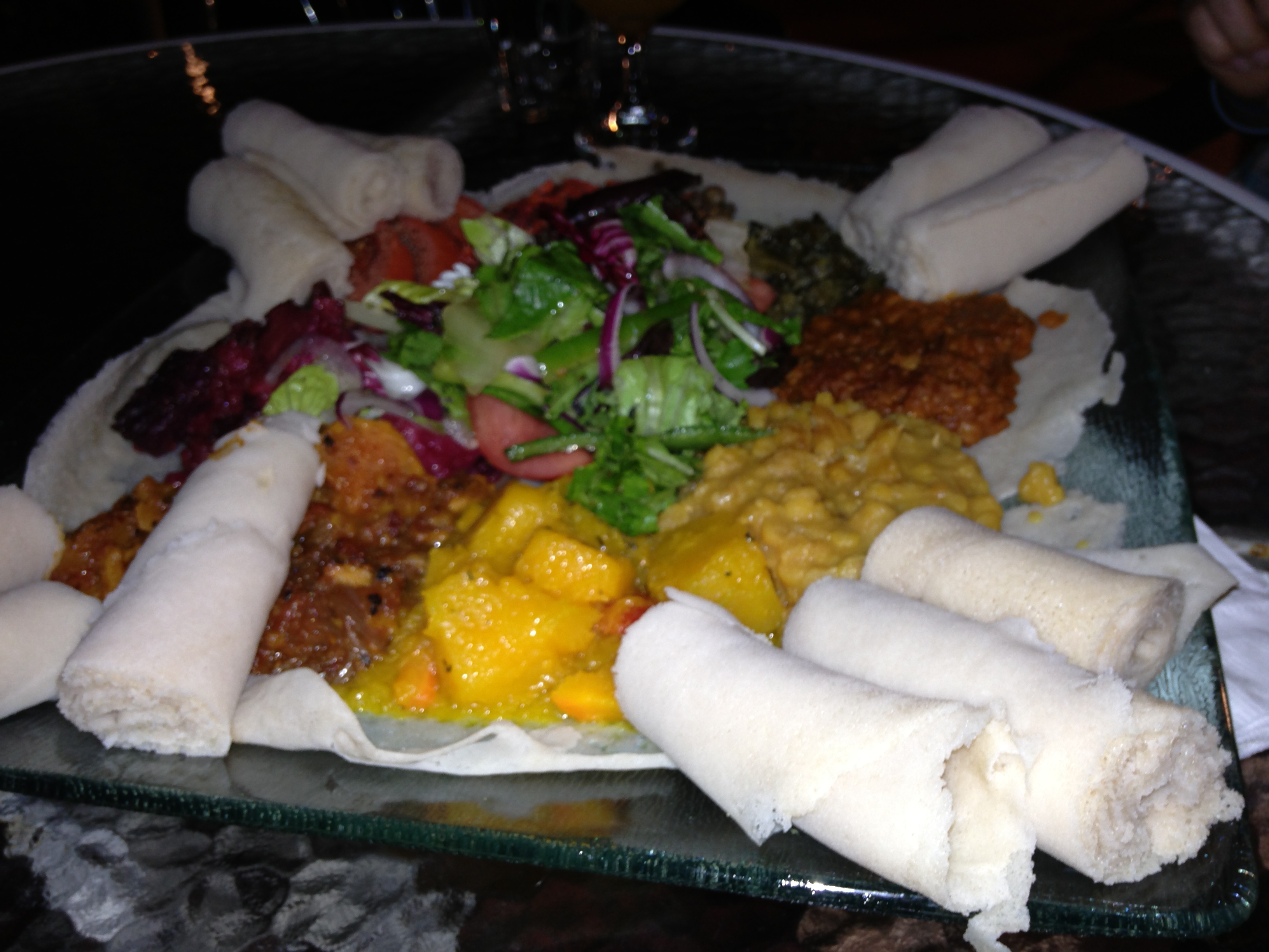 "Those rolled up parts are injera (Ethiopian ""bread"") to use to eat the rest of the meal"